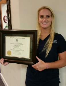Whitney Cazalas pictured with her certificate from the Board of Dental Examiners of Alabama, indicating her new status as fully licensed dental hygienist.